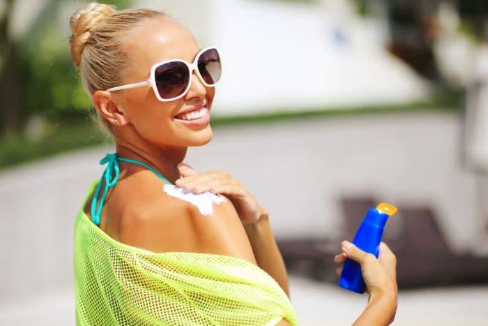Девушка наносит солнцезащитный крем на плече
