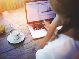 Девушка перед ноутбуком с чашкой кофе