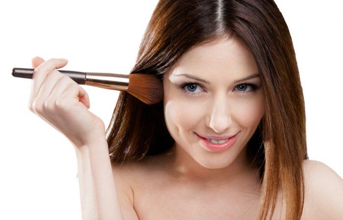 Девушка с кисточкой для макияжа на белом фоне