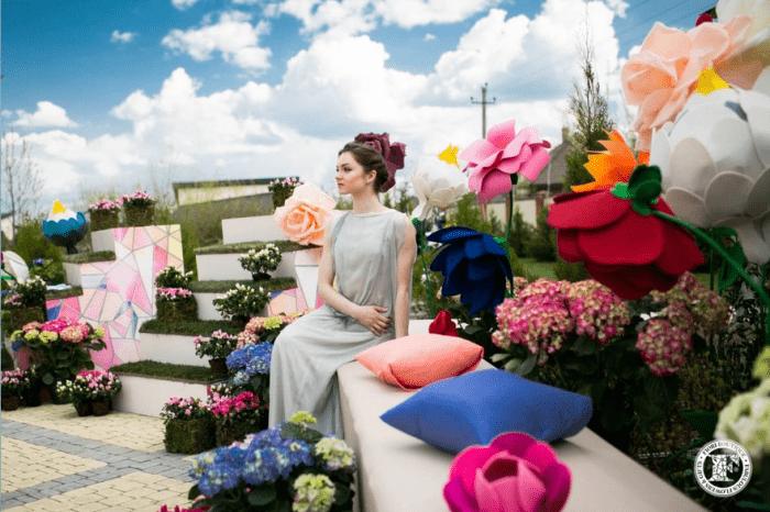 Девушка сидит возле больших цветных искусственных цветов