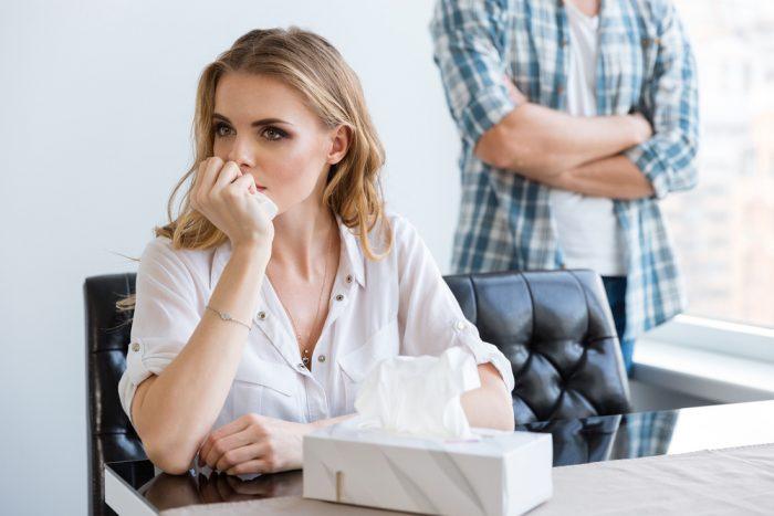 Девушка сидит за столом с коробкой носовых платков