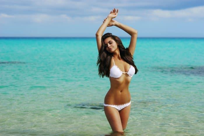 Девушка в белом купальнике стоит по колено в море