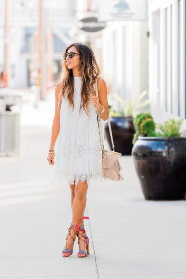 Девушка в белом платье и в босоножках с завязками