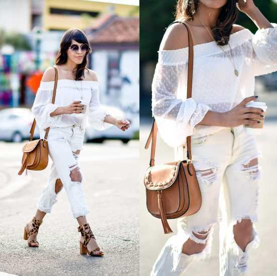 Девушка в белой кофте и белых джинсах идет с кофе