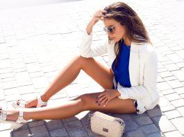 Девушка в синей майке, белых шортах и в белом пиджаку сидит на асфальте