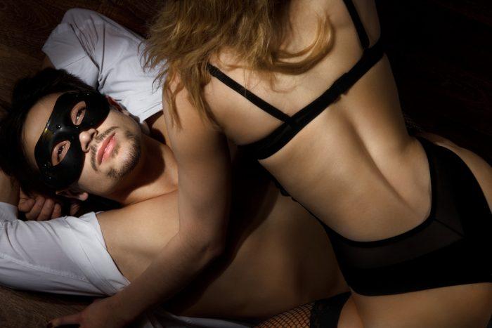 девушка в черном нижнем белье сидит на мужчине в черной маске