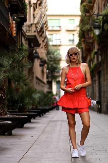 девушка в красном комбинезоне с баской и белых кроссовках
