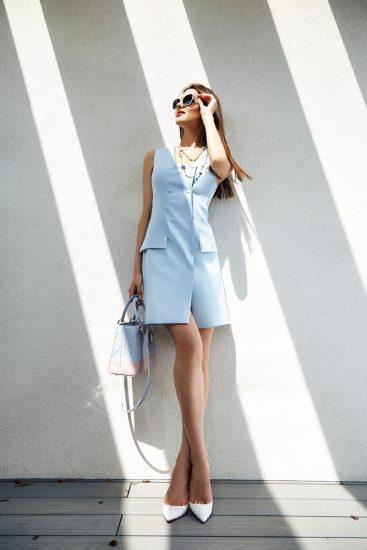 Девушка поправляет очки в платье- пиджаке голубого цвета