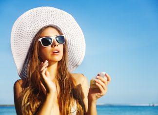 Девушка на море в шляпе и в очках наносит крем на лицо