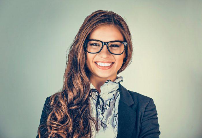 Девушка в очках, рубашке и пиджаке улыбается на сером фоне