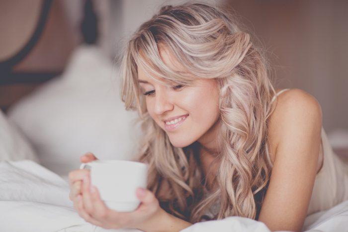 Девушка в постеле пьет чай