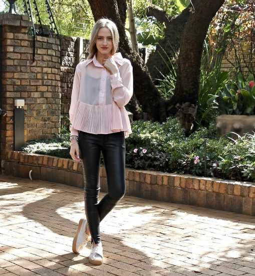 Девушка в розовой кофте и кожаных штанах
