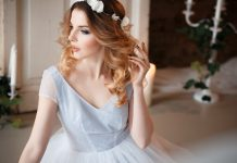 Девушка в серо-голубом платье и с венком из белых цветов на голове