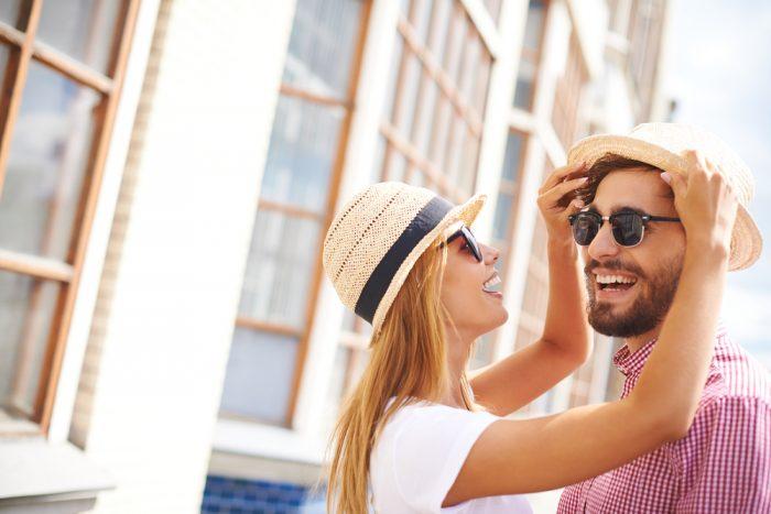 Счастливая девушка и ее бойфренд в головных уборах и солнцезащитных очках