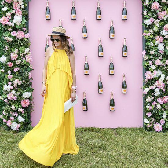 девушка в желтом платье и шляпке стоит на фоне бутылок