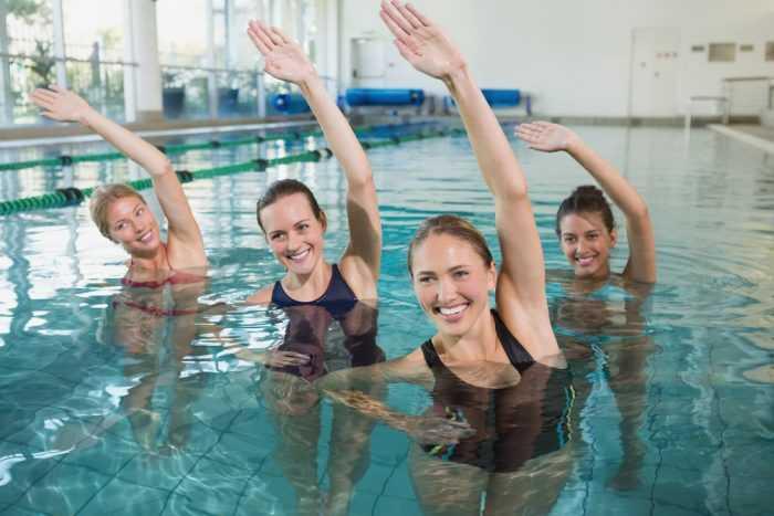 Женщины подняли руки и делают упражнения в бассейне