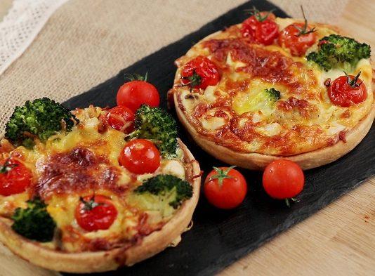 Два французских пирога киш на черной доске с помидорами