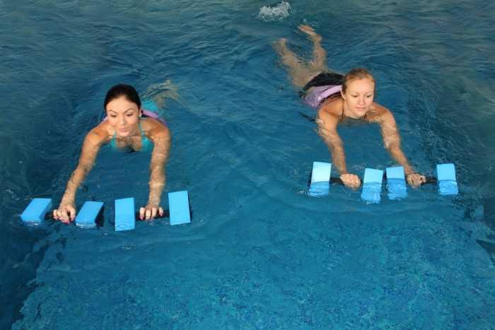 Две девушки плавают в бассейне с гирьками