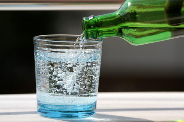 Из стеклянной зеленой бутылки наливают воду в стакан