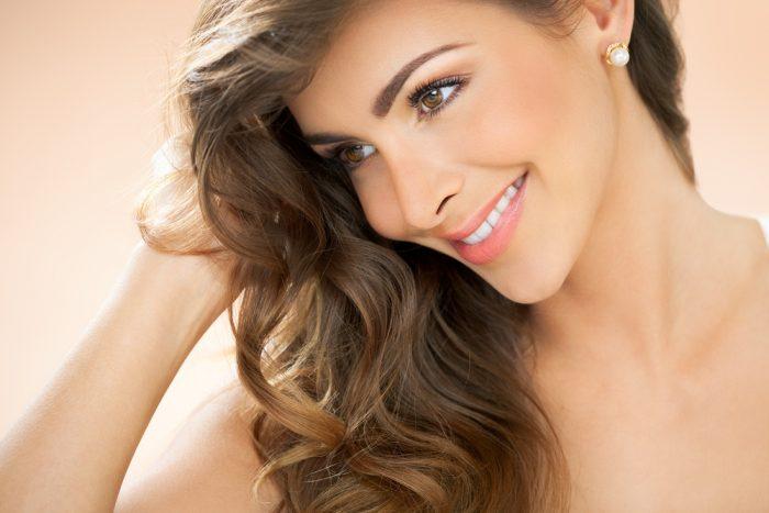 Красивая женщина с жемчужными серьгами мило улыбается