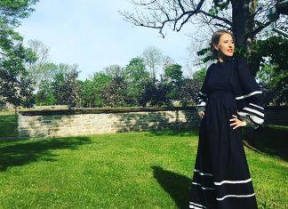Ксения Собчак стоит на зеленной траве в длинном платье