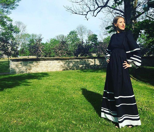 Ксения Собчак стоит на зеленой траве в длинном платье
