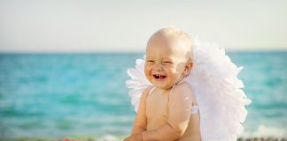 Маленький мальчик с крылышками ангела сидит на берегу моря