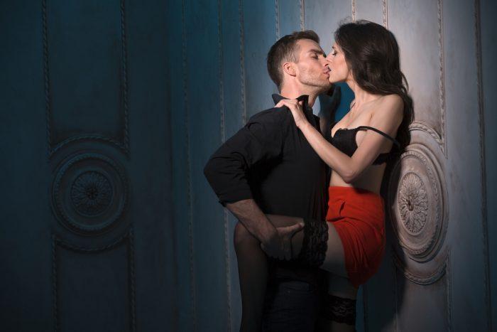 Мужчина целует девушку в красной юбке