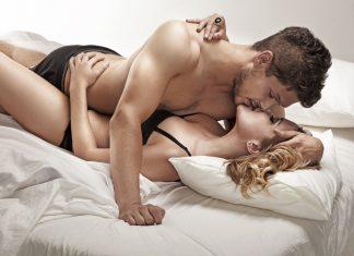 Мужчина с женщиной целуются в постеле