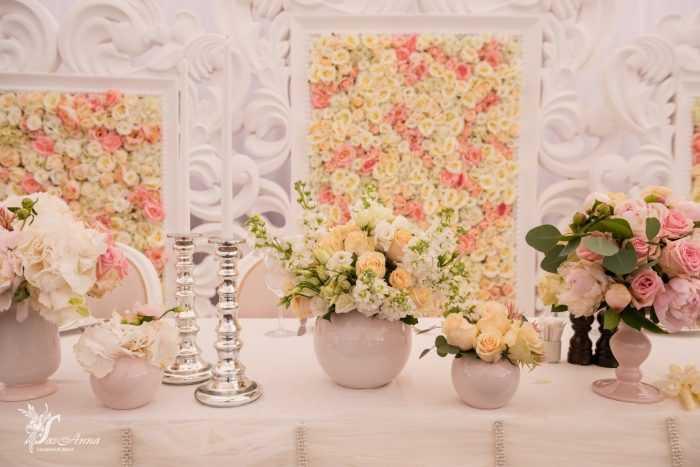 Оранжевые и розовые розы в вазах и на стенах