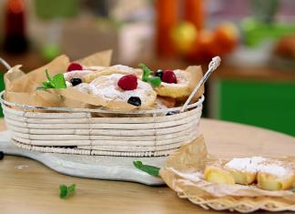 Пончики посыпанные сахарной пудрой и ягодами в белой корзинке