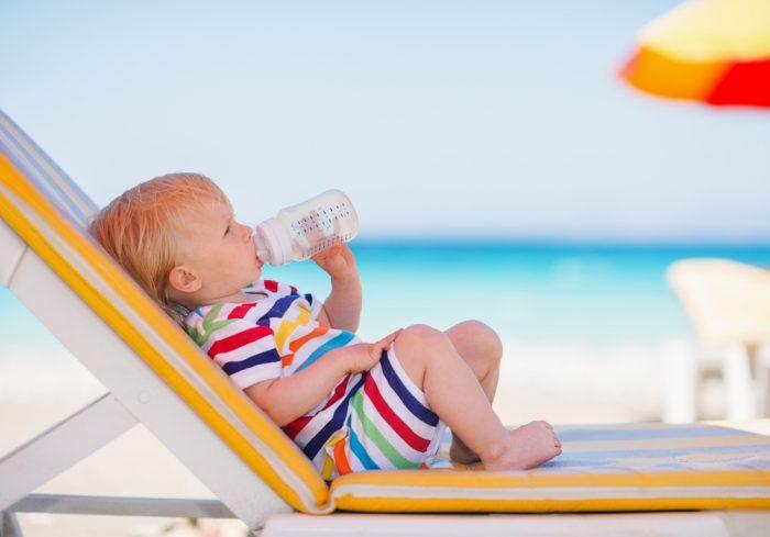 Ребенок в полосатом костюме лежит на лежаке с бутылочкой воды