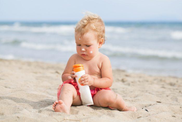 Ребенок сидит на песке с бутылочкой крема