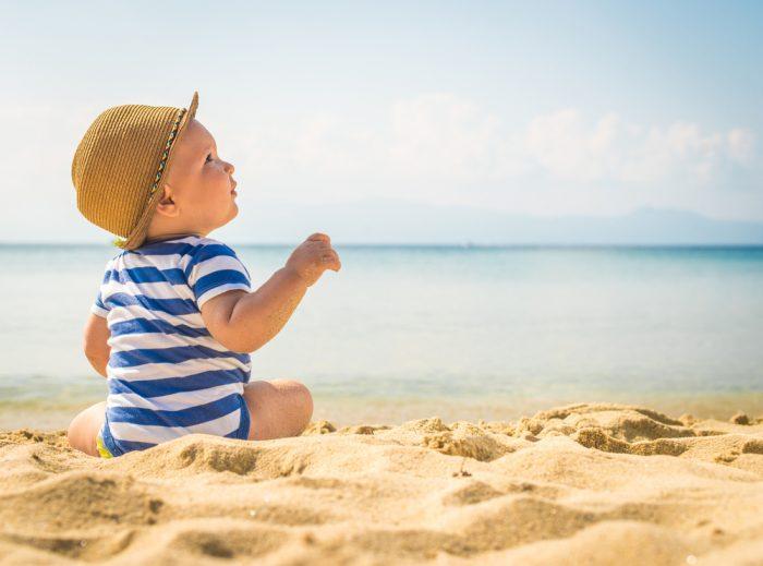 Ребенок в полосатом костюме и в шляпке сидит на песке