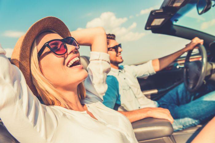 Счастливая девушка едет возле парня в машине
