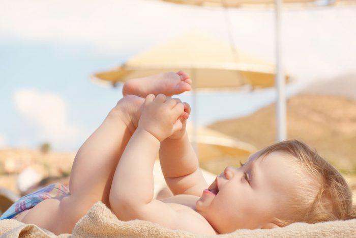 Счастливый ребенок лежит на пляже