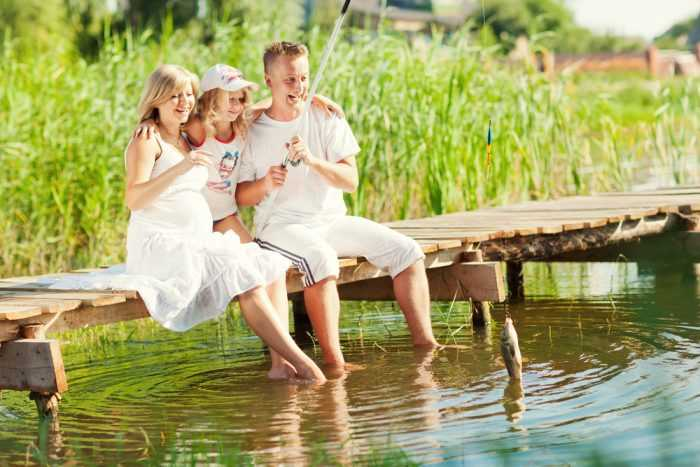 Семья сидит на мостике и мочит ноги в воде