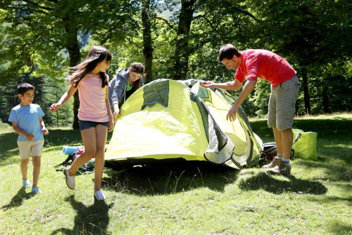 Семья ставит палатку в лесу