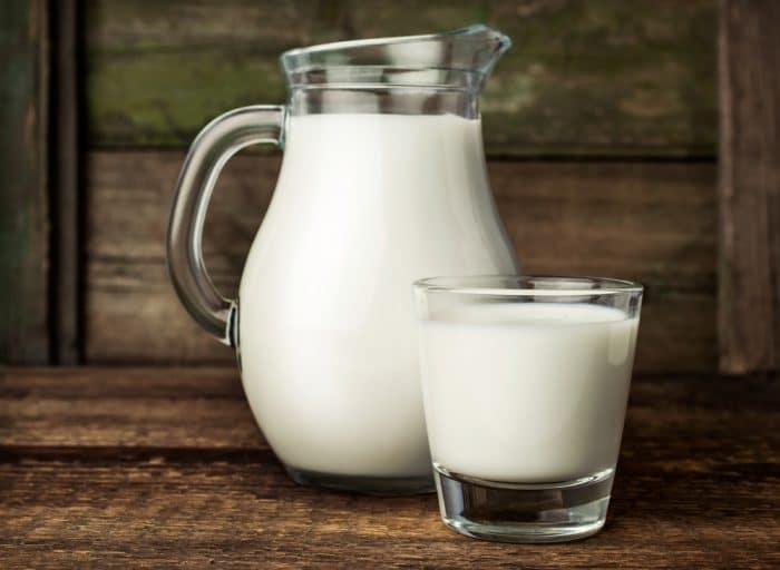 Стакан молока возле графина на деревянном столе