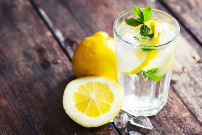 Стакан воды с дольками лимона и листочкочком мяты на деревянном столе