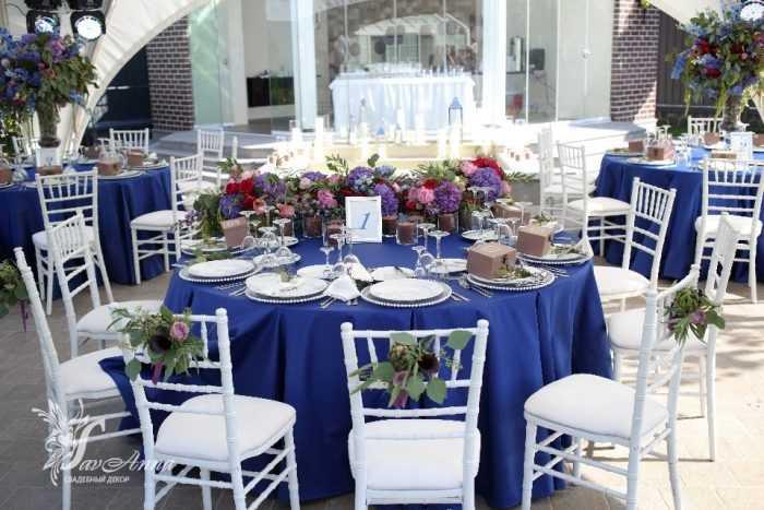 Столики с синей скатертью и цветами