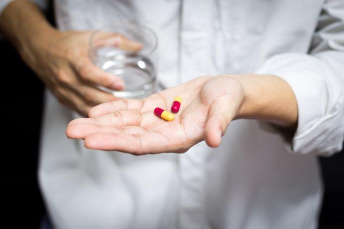 Таблетки с стаканом воды в мужских руках