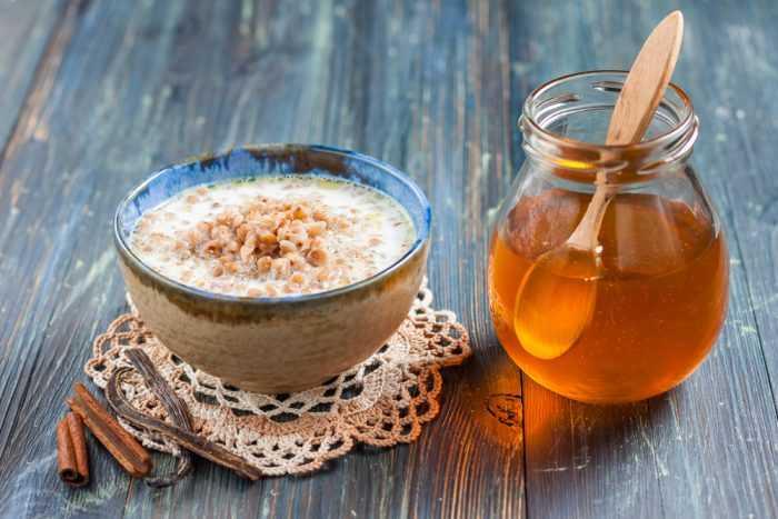 Тарелка овсяной каши возле баночки с медом на деревянном столе