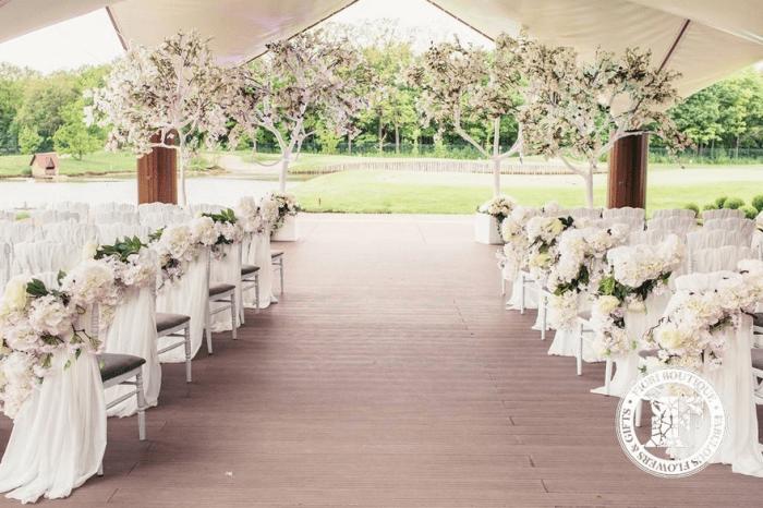 Терраса с украшеными стульями и деревьями для венчания
