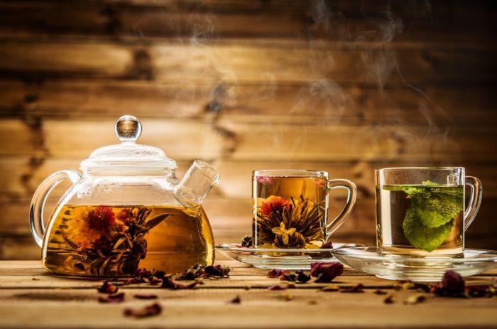 Травяной чай в двух чашках и чайничке на деревянном фоне