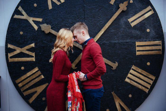 Пара держится за руки напротив больших часов