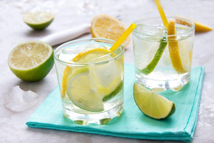 Вода в стаканах на салфетке с лимоном и лаймов