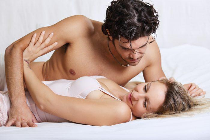 Женщина отталкивает мужчину в постеле