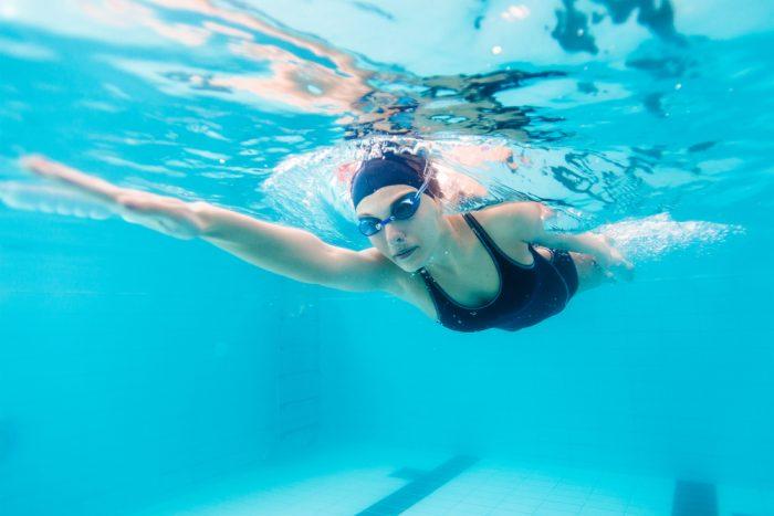 Женщина привет в шапочке для плавания и очках под водой в бассейне