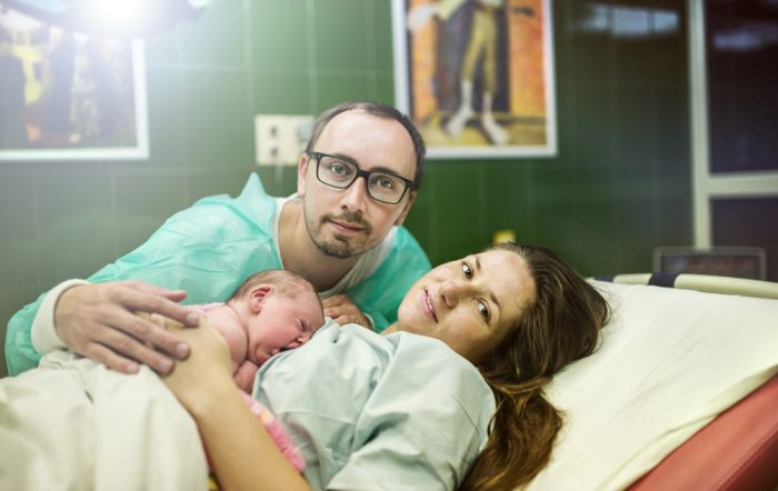 Ребенок несколько минут после рождения вместе с матерью и отцом в больничной палате